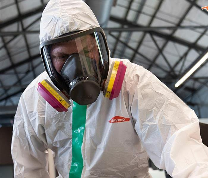 SERVPRO employee dressed in white biohazard suit and mask
